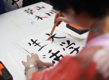 A woman paints Japanese characters.