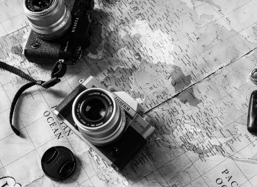 Two cameras rest on top of a world map. The photo is in black and white.