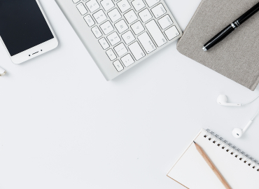 A wireless keyboard, phone, notebooks, pens and a pair of earphones on a white desk.