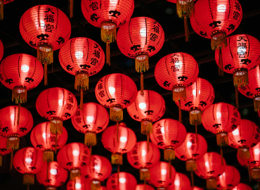 Red lanterns with Chinese characters hang from a ceiling.