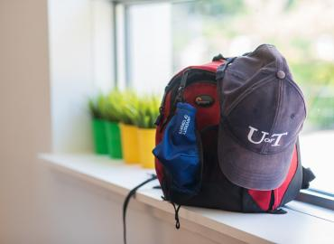 A red backpack, U of T hat and mask on a window sill.