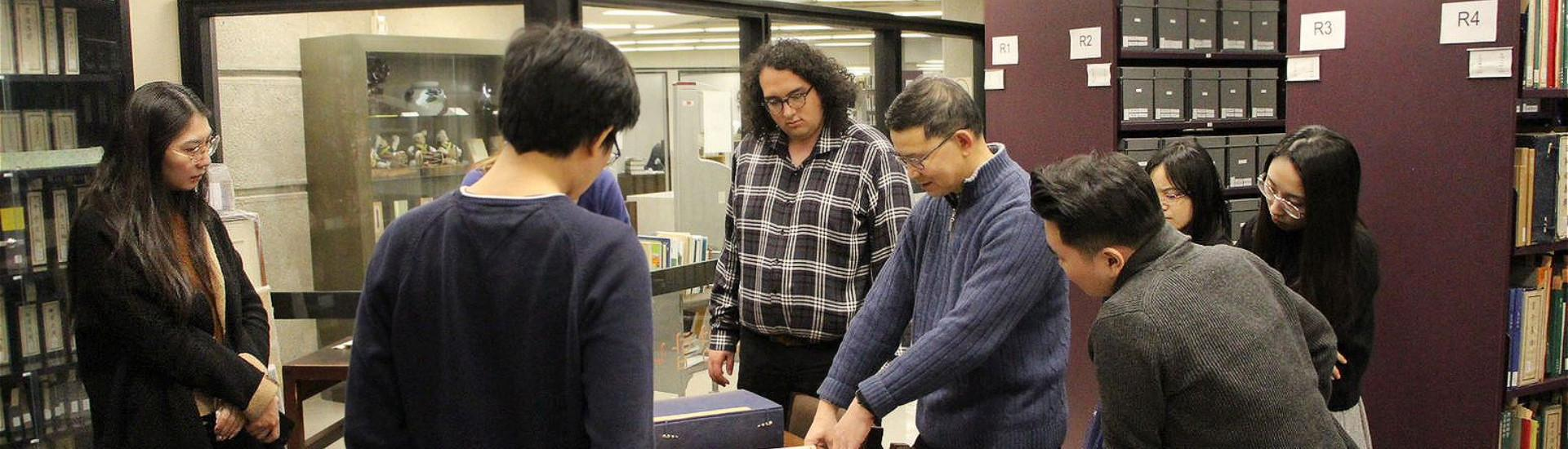 EAS graduate students looking at a book with a librarian at the East Asian Library.